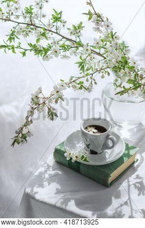 The Atmosphere Of A Romantic Spring Morning. Blooming Branches In A Vase, A Book And A Cup Of Coffee