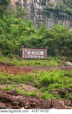Wushan, China - May 7, 2010: Dawu Or Misty Gorge On Daning River. White On Brown Sign Announcing The