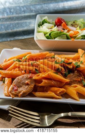 Italian Penne Alla Vodka Pink Cream Sauce With Sliced Spicy Sausage And Side Salad