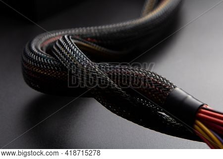 Cable snake skin. Black braided wires in bundle on black background. Braided Sleeving. Data line protection. Wire Flame-retardant nylon tube