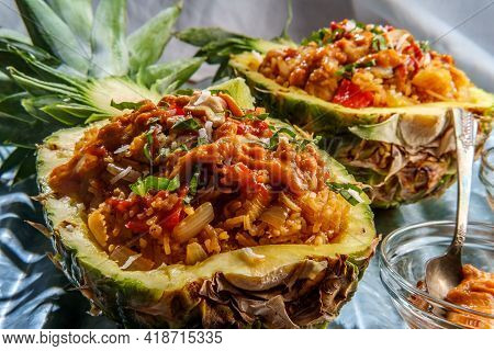 Thai Cashew Chicken Fried Rice Served In A Pineapple Bowl With Sriracha And Peanut Satay Sauce