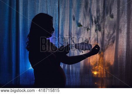 Silhouette Of A Pregnant Woman Removing A Medical Mask N95 After Recovering From An Illness. Pregnan