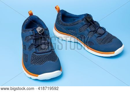 New Blue Kids Sneakers With Rubber Sole On Blue Background, Closeup.