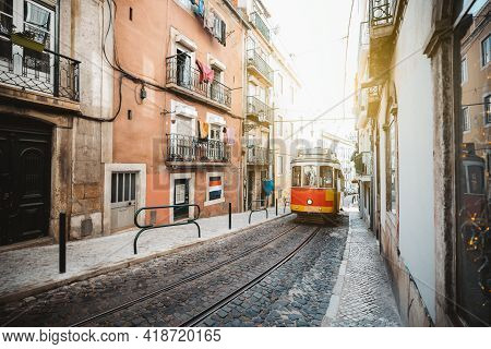 A Wide-angle View Of A Red Retro Tram On A Narrow Street With One-way Rail Traffic In A European Cit
