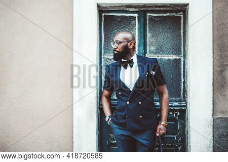 A Handsome Dapper Bald Black Guy With A Beard, In An Elegant Dark-blue Suit With A Bow-tie And Glass
