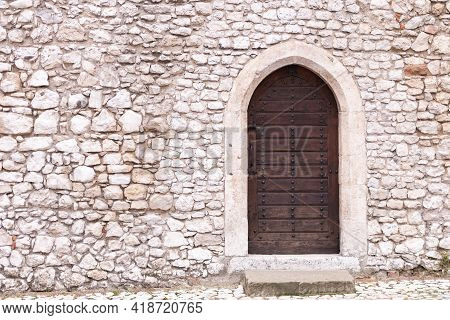 Stone Wall With Door. Old Masonry And An Old Wooden Door In The Castle Wall. Back Entrance To One Of