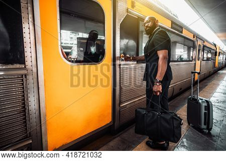 A Wide-angle View Of A Mature Bald Bearded Black Man Entrepreneur In A Suit And With Luggage Bags, P