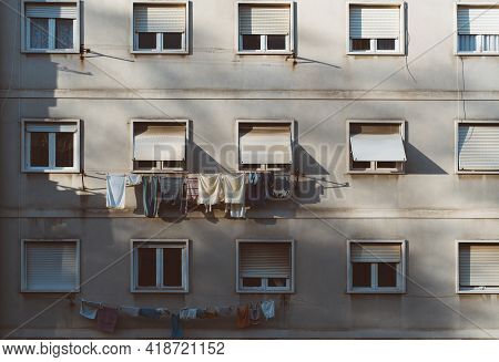 A Greyish House Facadeof A European Residential House In Uptown With Many Windows, Part Of Which Is