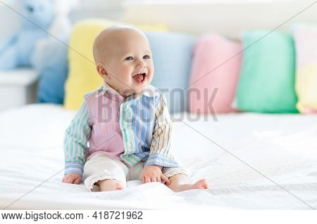Baby Boy In White Bedroom. Newborn Child In Bed With Pastel Color Cushions. Nursery For Children. Te