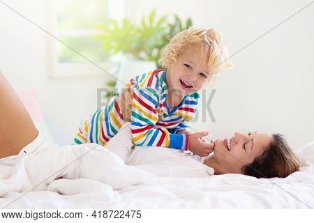 Mother And Child Playing In Bed On Sunny Morning. Mom And Baby Relaxing In White Bedroom At Home. Yo