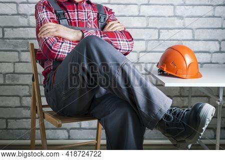 Striking Worker On Workplace. Worker On Strike Against Brick Wall Background. Work Refusal Concept.