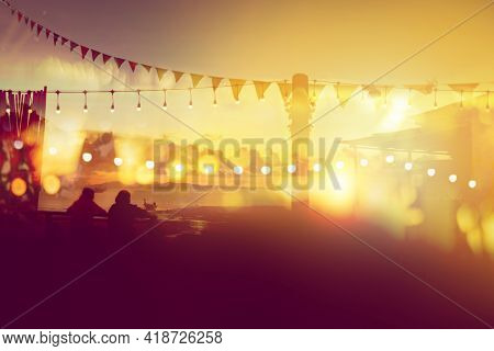 Two Friends Watching Sunset At Restaurant On The Beach, Blurred Bokeh Light On Sunset With Yellow St