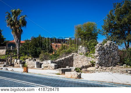 A Beautiful Green Tree, Palms Against A Blue Sky On A Warm Summer Day, Grows In The Ruins Of An Anci