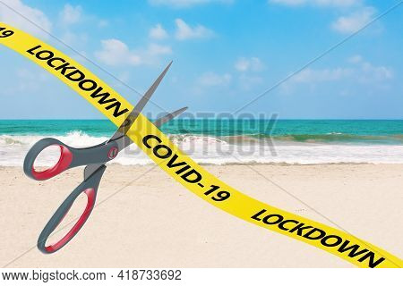 The End Of Lockdown Concept. Scissors Cut Yellow Ribbon With Covid-19 Lockdown Sign On An Ocean Beac