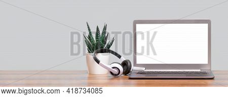Laptop. Mockup Screen And Headphones On Wooden Desk And Plain Background Banner. Distant Learning. W