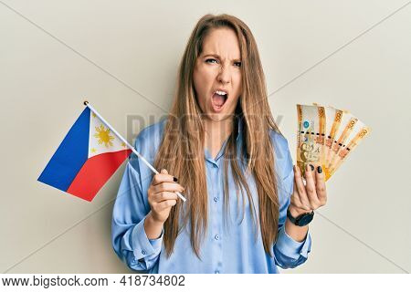 Young blonde woman holding philippine flag and philippines pesos banknotes in shock face, looking skeptical and sarcastic, surprised with open mouth