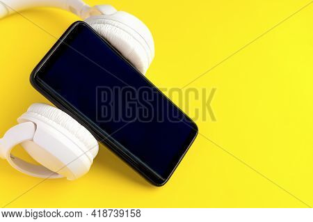 Close-up And Selective Focus Of Phone And White Wireless Headphones On Bright Yellow Background. Con