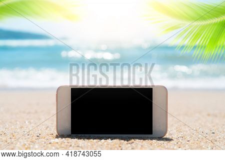 Smart Phone On Tropical Sand Beach With Palm Leaf And Bokeh Sunlight Wave Abstract Background. Black