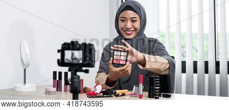 Asian Muslim Woman Beauty Blogger Looking At The Camera To Review Eye Shadow Showing On Her Hand And