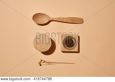 Organic Facial Scrub Next To Wooden Spoon And Dry Flower On Light Orange Background, Flat Lay, Top V