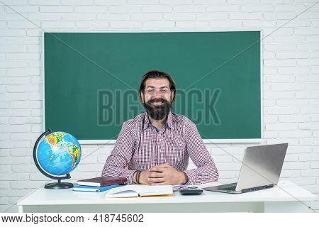 Back To School. Informal Education. Happy Mature Teacher Working On Computer. Brutal Bearded Man Wor