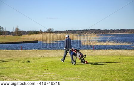 Latvia, Riga, April, 2021 - People Playing Golf On The Banks Of The Beautiful Kisezers Lake In Riga,