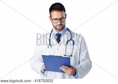 Shot Of Male Doctor Holding Clipboard In His Hand And Working While Standing On The Clinic's Foyer.