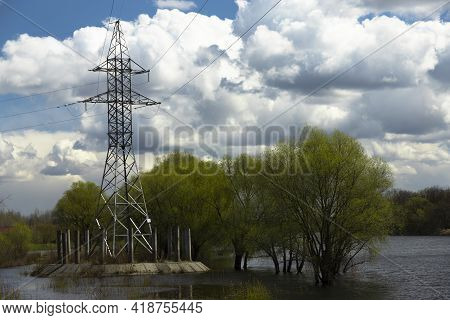 Power Lines, Poles And Trees Are Flooded During The Flood In The River.
