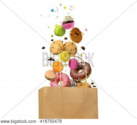 Donuts, Cookies, Macaroons And Other Sweets Falling In Paper Bag Isolated Over White Background. Swe