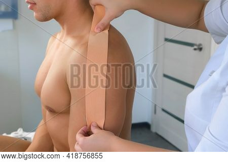 Physiotherapist Is Applying Kinesiology Tape To Man Patients Shoulder In Clinic, Closeup. Using Of T