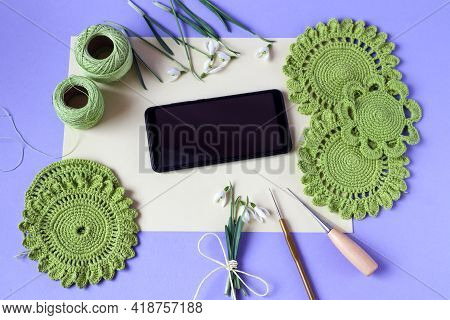 Phone Among The Needlework Motifs Of Green Color And Objects For Needlework, Top View-the Concept Of
