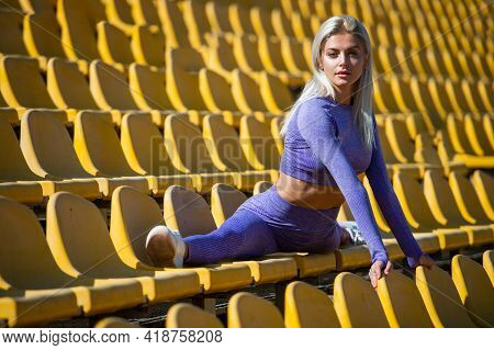 Athletic Woman In Fitness Wear Sit In Split On Stadium, Stretching