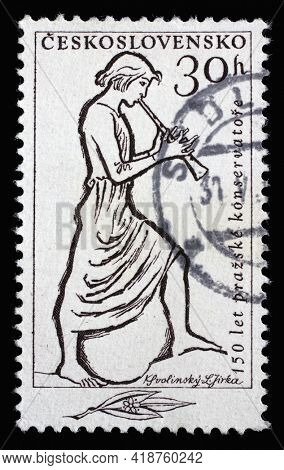 ZAGREB, CROATIA - SEPTEMBER 18, 2014: Stamp printed in Czechoslovakia shows Flute Player, series honoring 150 years of Prague Conservatory, circa 1961