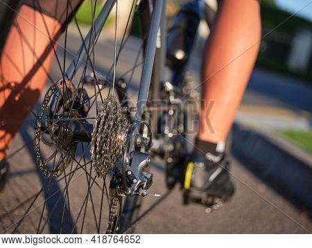 Close Up Shot Of Bicycle Speed Rear Cassette With Chain And Brake Disk. Cyclist Riding Road Bike On