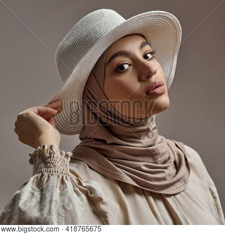 Fashionable Young Arabian Girl In Hijab And Hat Posing On Light Background And Looking At Camera. Be