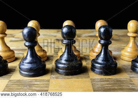 Black And Yellow Wooden Pawns On A Chessboard.