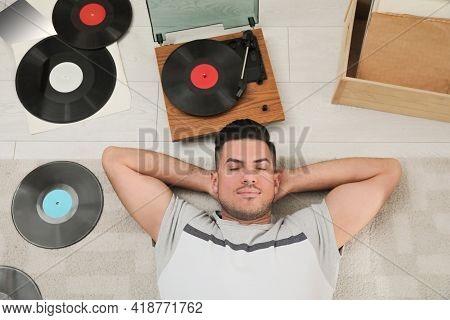 Man Listening To Music With Turntable While Lying On Floor At Home, Above View