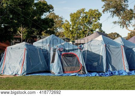 Tents Setup For A Group Camping At The Green Grass Meadow. Multiple Blue Instant Up Connectable Tent
