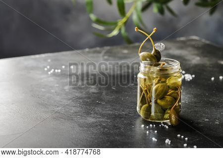 Capers. Marinated Or Pickled Canned Capers Fruit Close Up In Glass Jar On Gray Kitchen Table Backgro