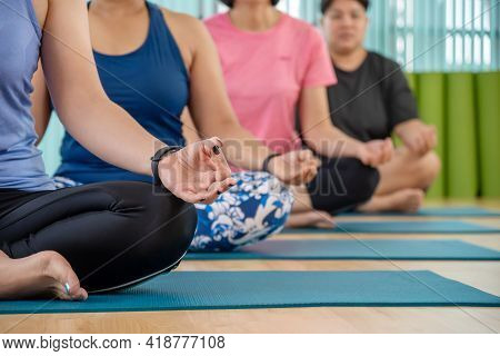 Time For Yoga. Attractive Young Woman Exercising And Sitting In Yoga Half Lotus Pose With Mudra Gest