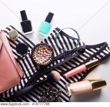 Stylized feminine flatlay with glasses, foundation, lip gloss, powder, brush, handbag, striped shirt
