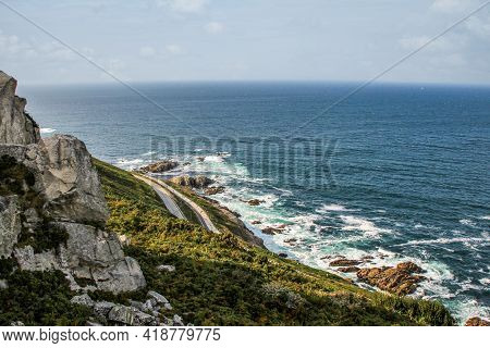 Coastal Road Bordering The Sea And Surrounded By Rocky Mountains In Galicia, Spain