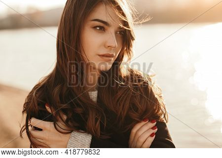 Pensive Young Long Haired Female In Warm Coat Looking Away Thoughtfully While Standing Near Lake At