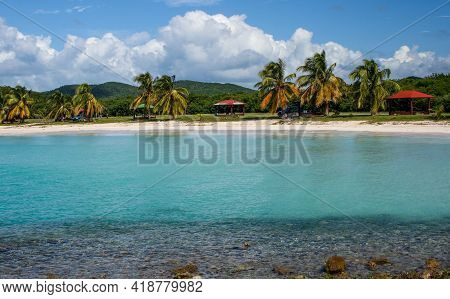 White Sandy Beach And Turquoise Water With Red Tents And Palm Trees In Puerto Rico
