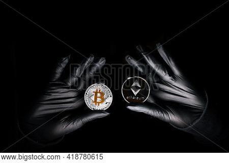 Hands In A Black Gloves Holding Bitcoin And Ethereum Coin Against Black Background. International Ha