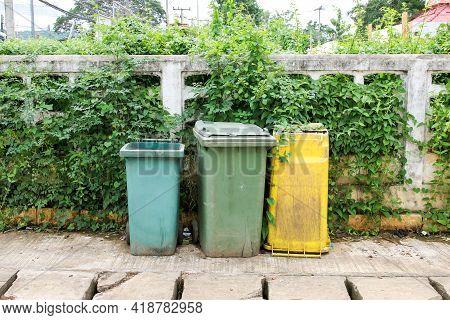 Municipal Waste Bins Are Beside Wall On The Roadside
