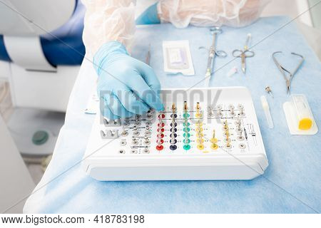 Set Of Instruments For Dental Implantation On The Table At The Dentist. Doctor In Blue Gloves Choose