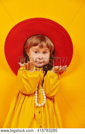 Cute little girl fashionista. Lovely little girl in red hat and yellow dress looks at the camera and is surprised. Happy childhood.