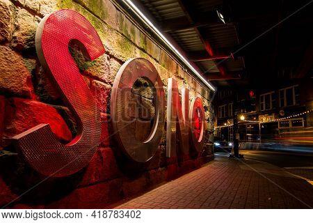 NORWALK, CT, USA - APRIL 24, 2021: SONO - South Norwalk sign under railroad bridge on Washington Street  with evening lights