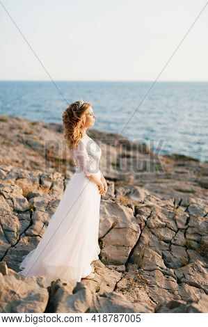 A Refined Graceful Bride With A Diadem Stands On A Rocky Seashore, The Suns Rays Fall On Her Face